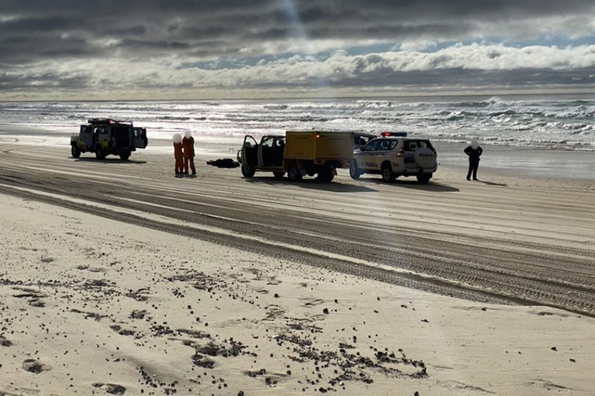 Police and paramedics at the scene of a fatal 4WD vehicle rollover on Fraser Island.
