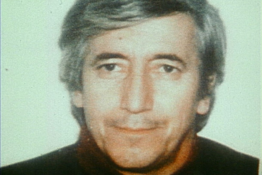 An archival photo of a man in his late forties with grey hair and a sweater on.