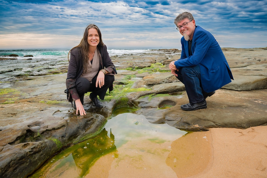 Dr Pia Winberg and Professor Gordon Wallace crouch down by the ocean.