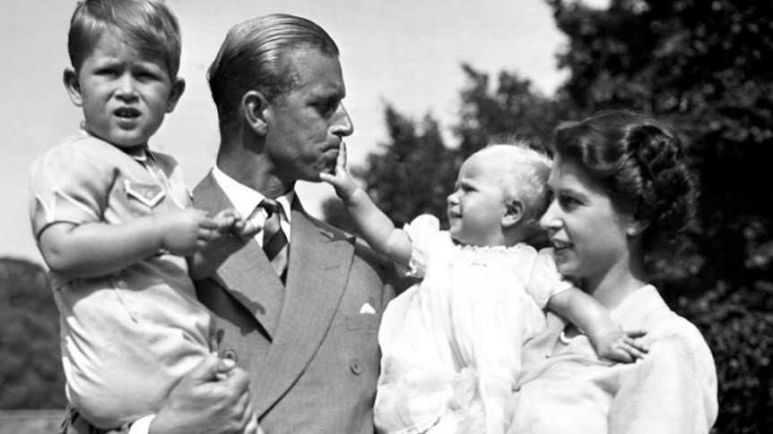 A black and white photo of a man holding a young boy and a woman holding a baby that is touching the man's mouth.