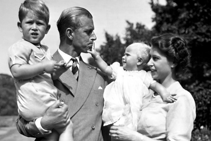 A black and white photo of Prince Philip holding boy Charles and Princess Elizabeth holding baby Anne.