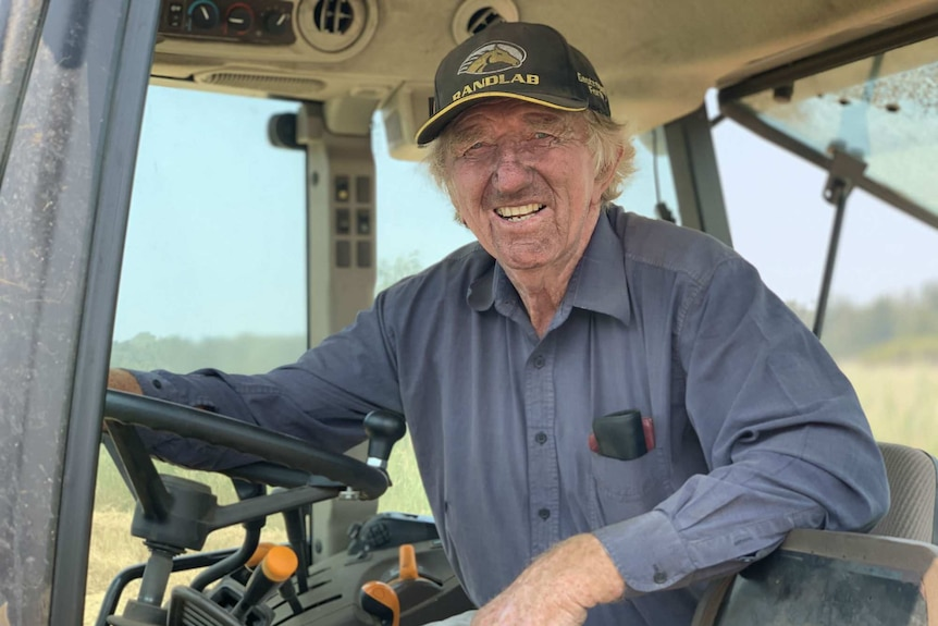 A man in a blue shirt and baseball cap leans on the wheel while sitting in the cab of a tractor.