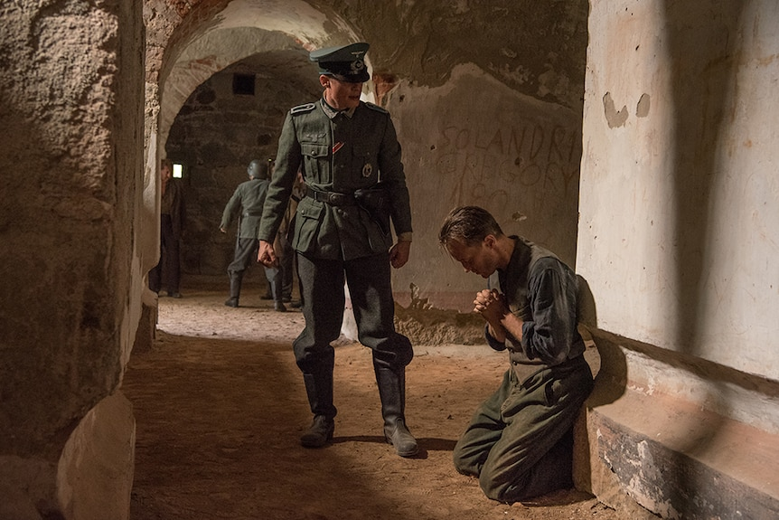 A man in World War II Nazi soldier uniform stands over man kneeling on floor with head bowed in dirt and concrete corridor.