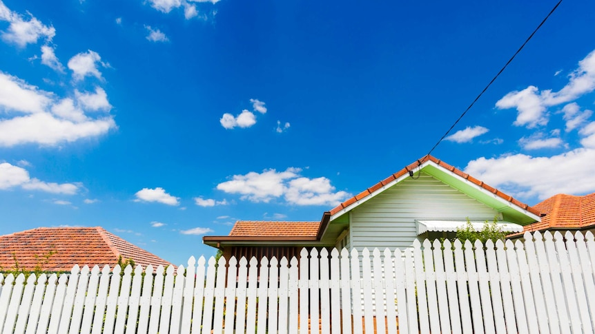 a house behind a white picket fence