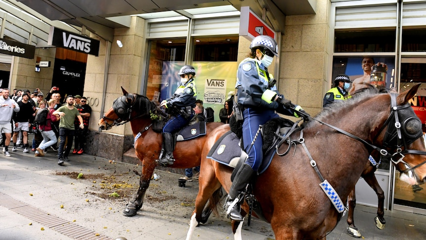 uniformed police wearing face masks on horseback are confronted by a group of anti-lockdown protesters in Sydney