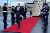 Australia Prime Minister Scott Morrison walks on a red carpet flanked by military personnel as he leaves a plane.
