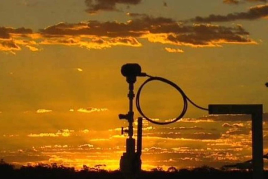 A coal seam gas well silhouetted against a golden sky