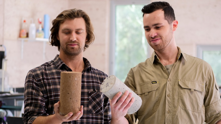 Two men looking at the small round blocks of cement they are holding in their hands