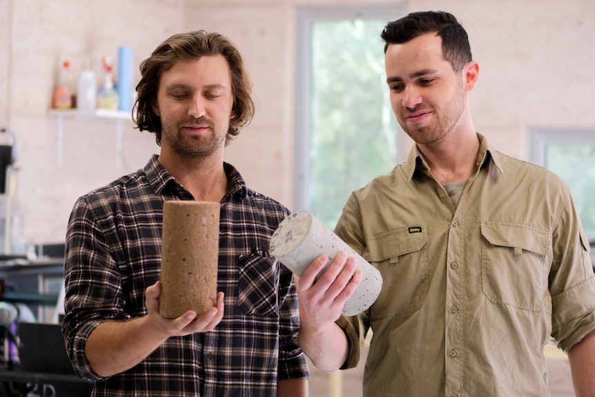 Two men looking at the small, round concrete blocks he is holding in their hands
