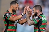 Two South Sydney NRL players touch hands as they celebrate a try against Brisbane.