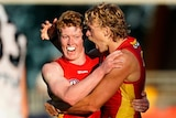two Gold Coast Suns players hug in celebration