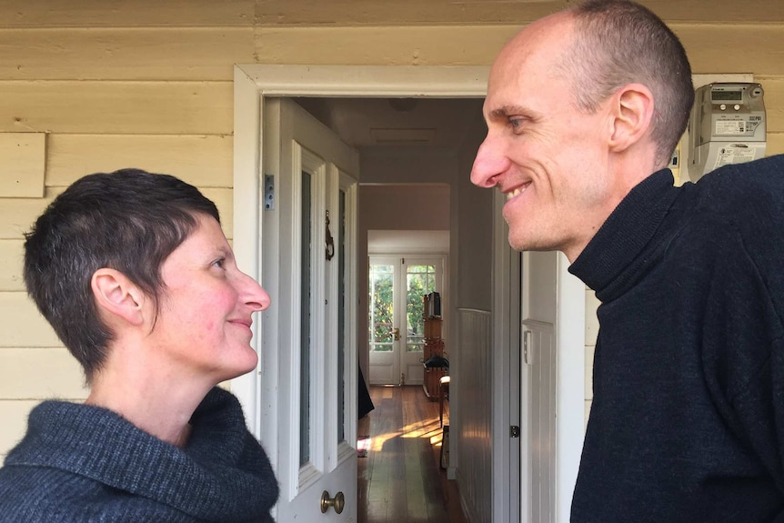 Rachael and Andy looking lovingly into each other's eyes outside their home.