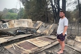 A man stands next to his burnt out home.