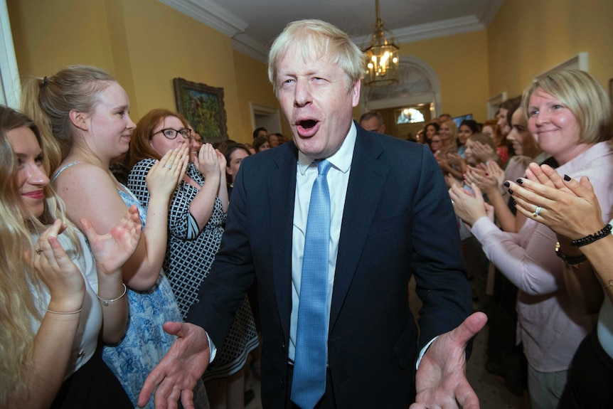 Boris Johnson pulls a gleeful face with his hands wide as he walks through a corridor surrounding by clapping staff.