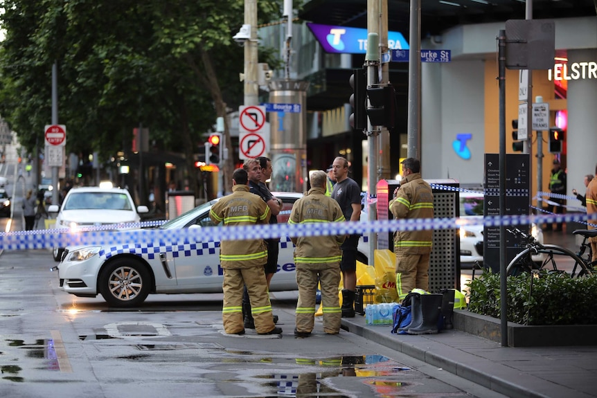 Emergency services staff at Bourke Street following a fatal stabbing.