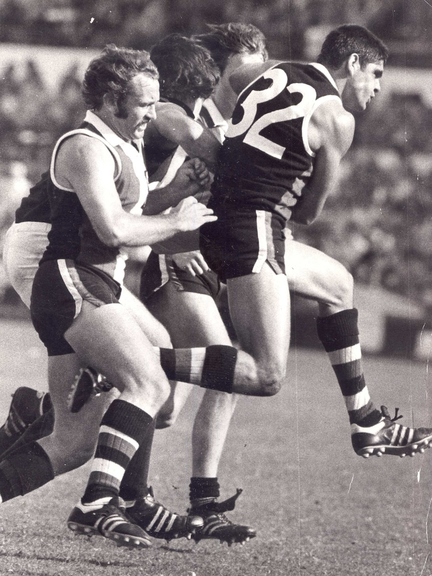 Four men jostle for the football in a VFL game.