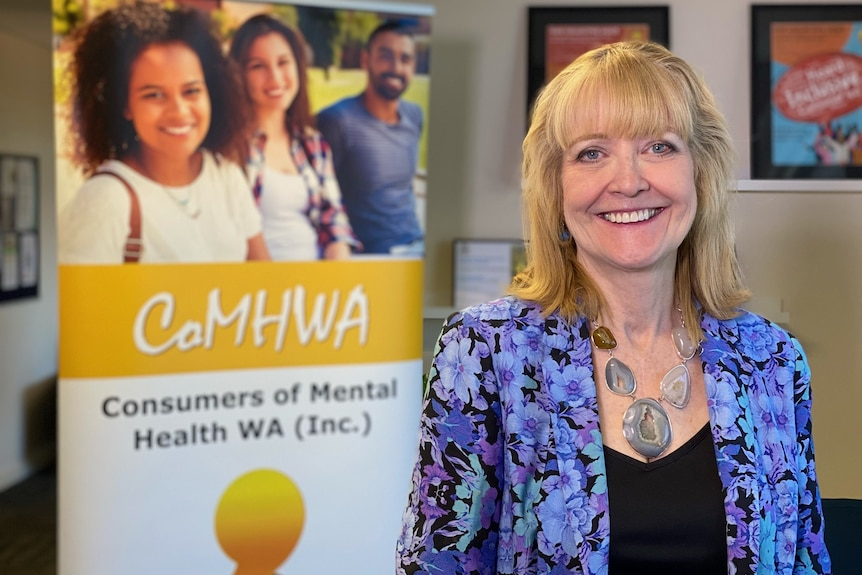 A smiling woman with blonde hair poses for a photo indoors in front of a Consumers of Mental Health WA poster.