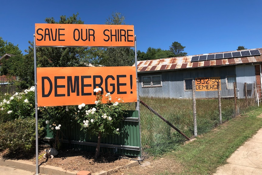 """Brightly coloured signs hung on a fence that read """"Save our shire"""" and """"DEMERGE!"""""""