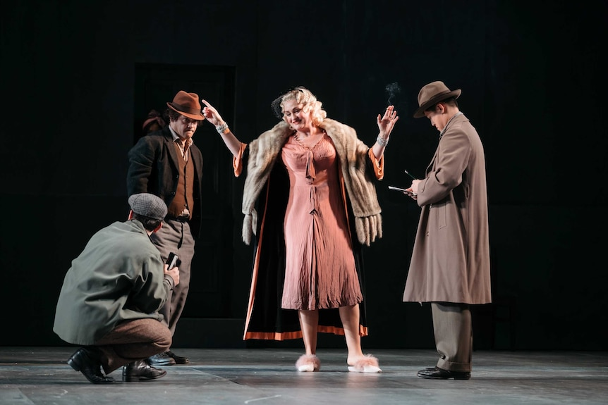 On stage a woman in 1920s formal outfit is surrounded by men