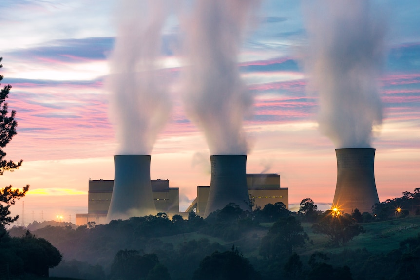 The silhouette of a power station is seen against the sky in the early evening, with thick smoke billowing from three towers.