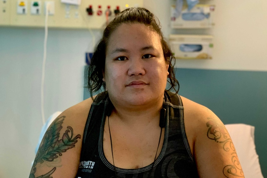 A woman sits in a hospital bed, facing the camera.
