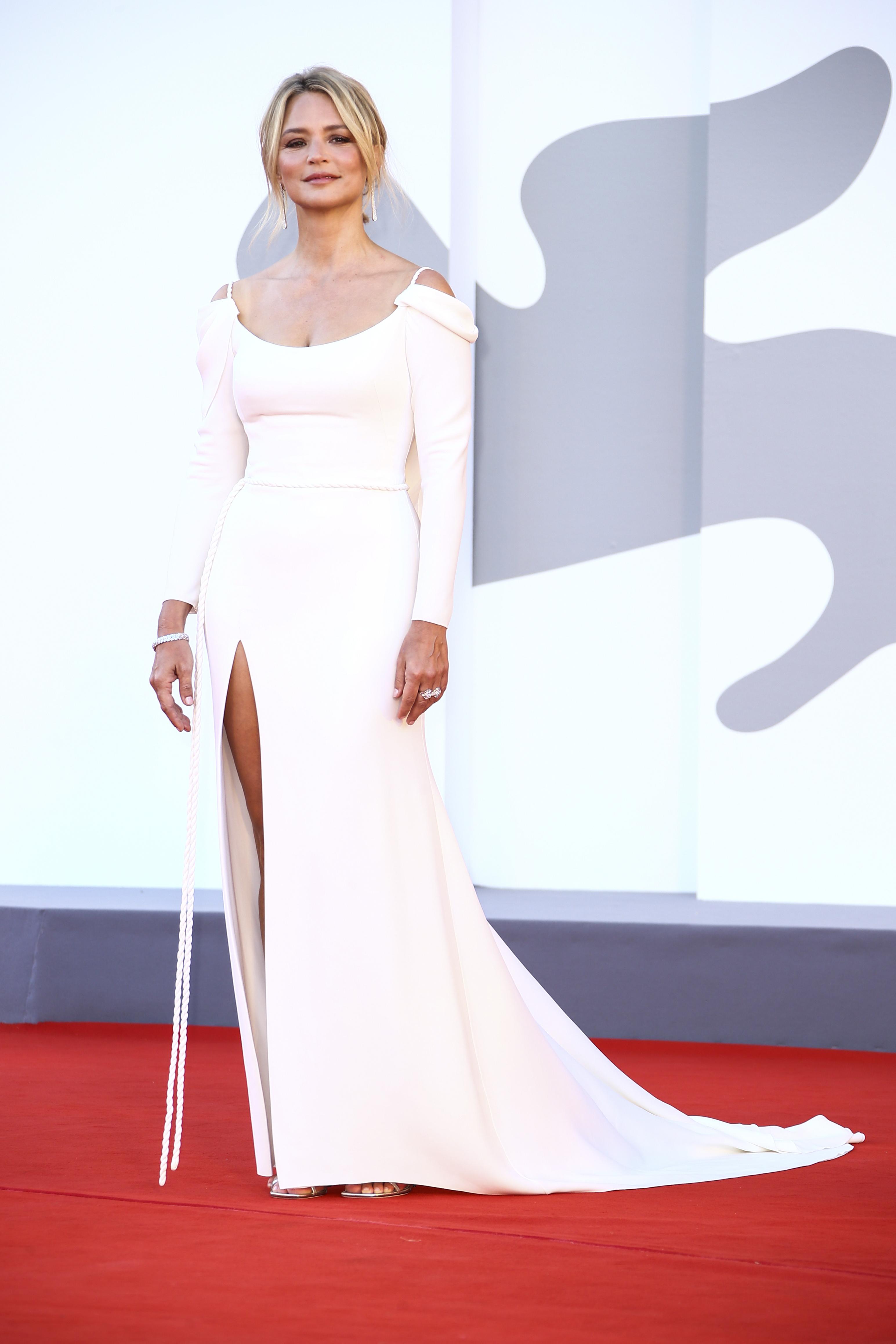 Virginie Evira indossa un abito bianco a maniche lunghe con spalle scoperte e uno spacco alto.
