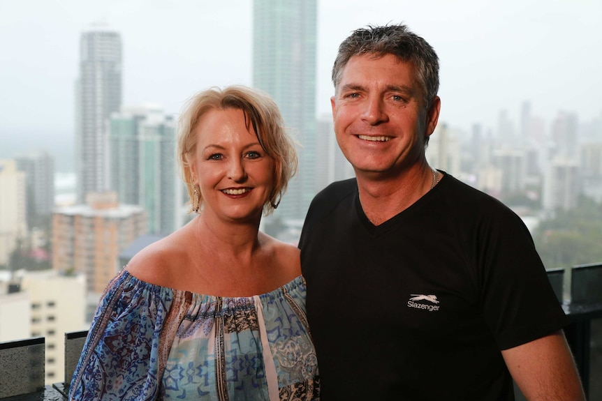 Michelle and Anthony Di Salvo stand on a high-rise balcony with the Gold Coast coastline in the background.