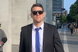 Matthew Paul Hockley, wearing sunglasses, walks in the street outside the District Court in Brisbane