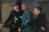 An image of the shooter being escorted from hospital.