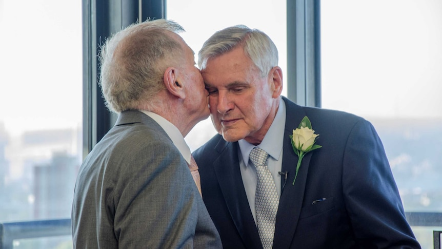 Two men hold hands and show their rings
