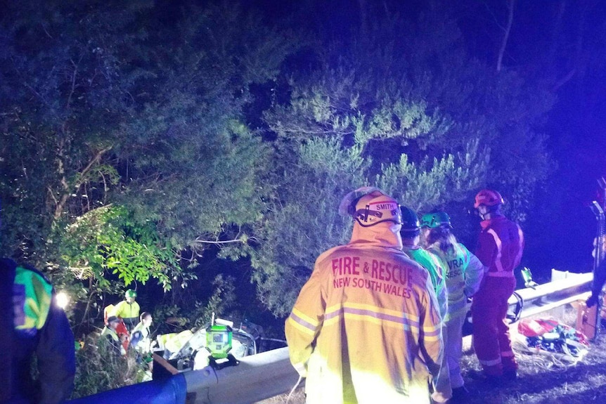 Emergency workers work to free woman from a car
