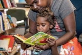 A photo of a mother reading a book to herchild.