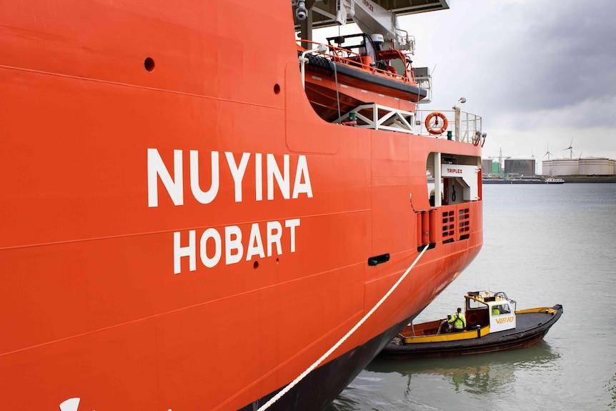A large orange ship with name Nuyina Hobart and small black tug boat.
