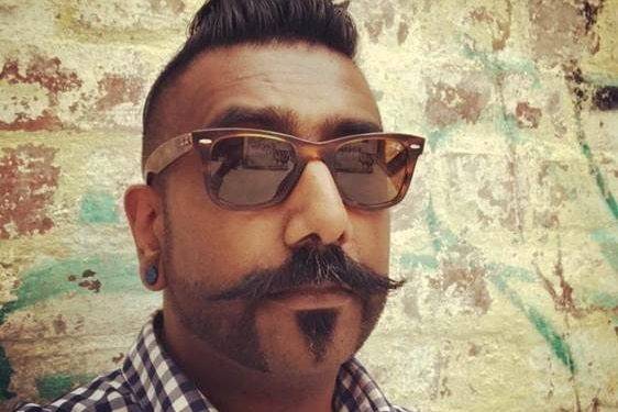 Samuel Jeyaseelan wearing sunglasses and taking a selfie in front of a brick wall.