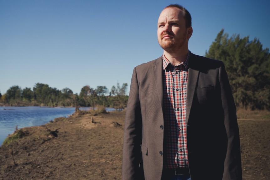 A mayor stands beside a flood-damaged river