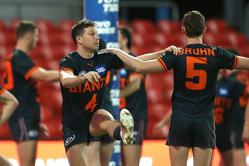GWS' Toby Greene holds onto his teammate's shoulder as he stretches his leg with a high kick.