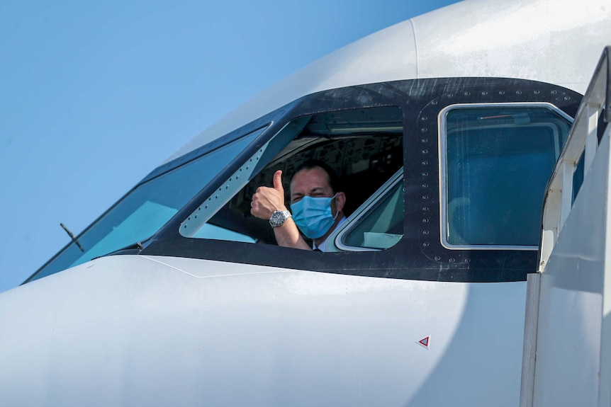 A pilot in a face mask giving the thumbs up out the window of the plane