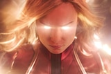 A close up portrait of Captain Marvel in costume with gold supernatural energy radiating from her eyes and around her head.