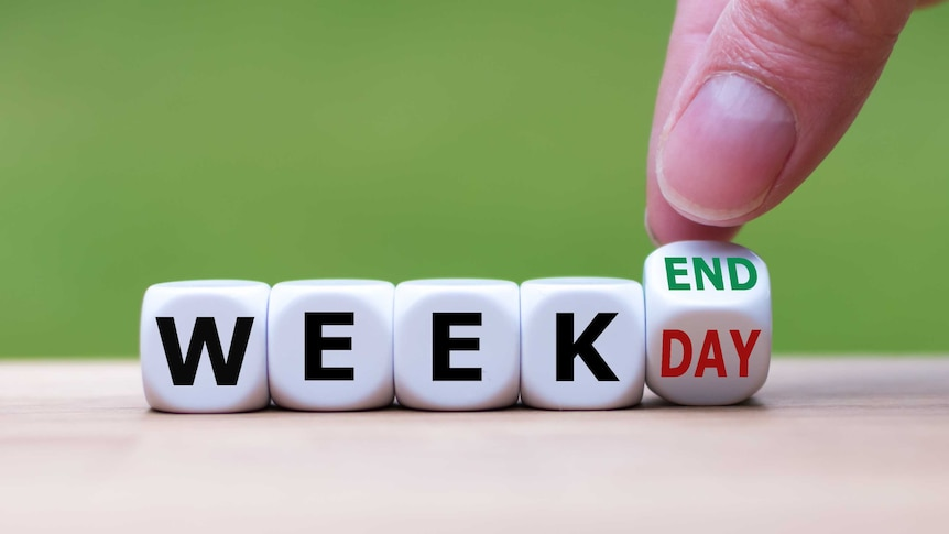 """A hand turns a dice and changes the word """"weekday"""" to """"weekend""""."""