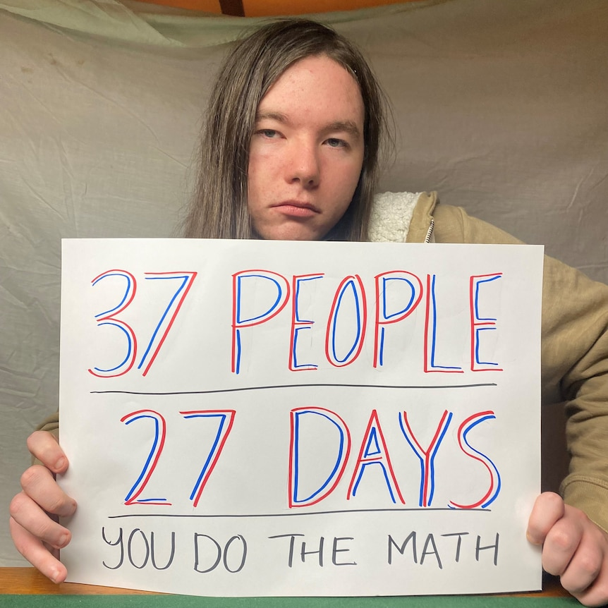 Whyalla Youth Group member Harold Flam sign reads '37 people, 27 days, you do the maths'.