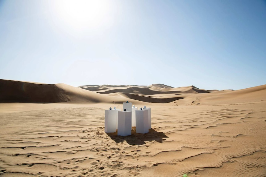 Seven white plinths sitting in a remote desert. An MP3 player sits on top of one plinth, while the others each support speakers.