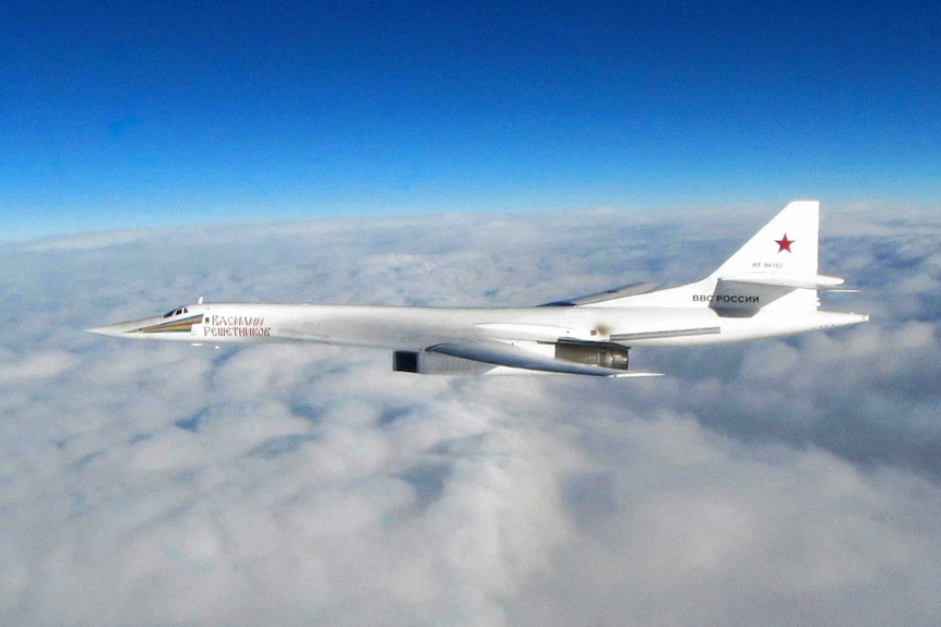 Wide shot of a Russian jet flying above clouds.
