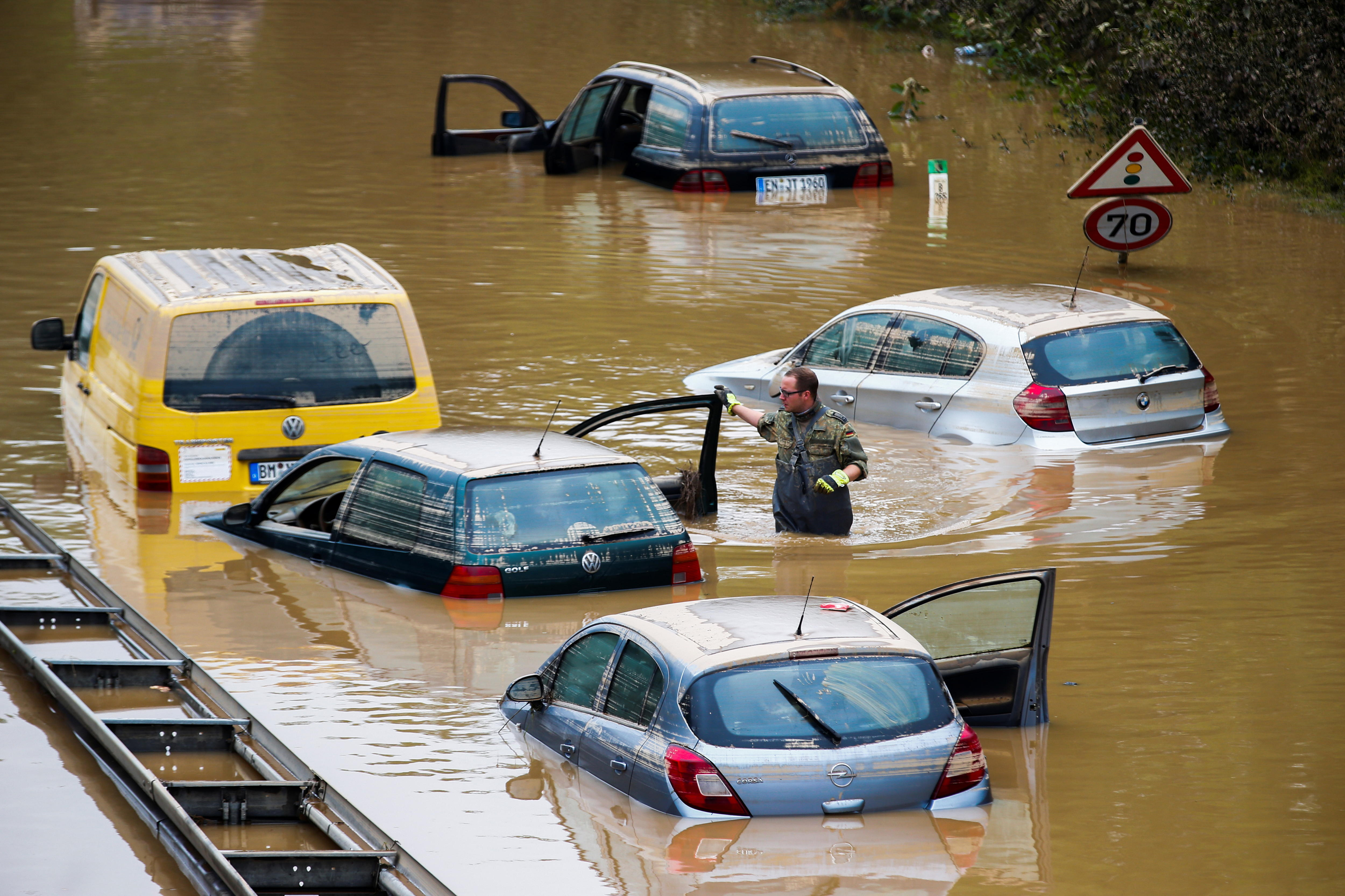 Rescuers search through cars submerged in floodwaters.