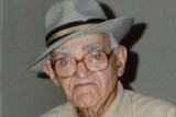 An elderly man, wearing glasses and a grey hat
