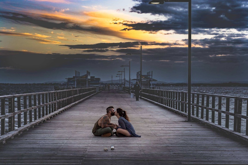 An unknown couple sitting down, kissing on Woody Point Jetty