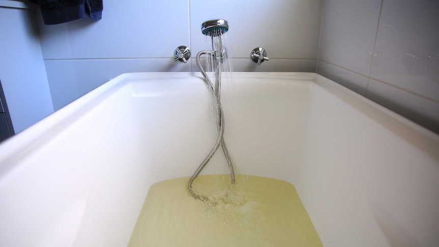 Discoloured, yellow water pours from the tap into a bath.