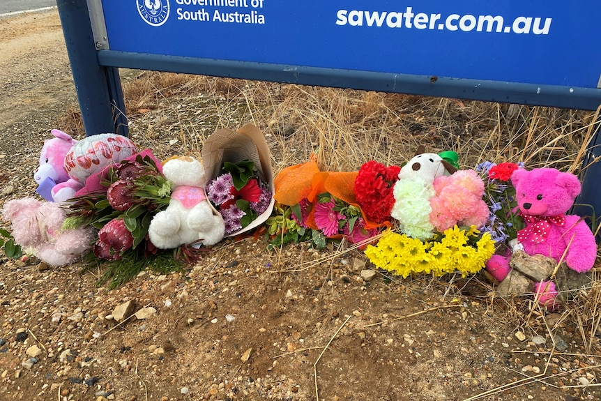 Flowers and teddy bears on the ground under a sign