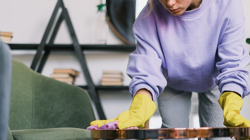 A woman in a purple jumper and yellow gloves wipes a small table