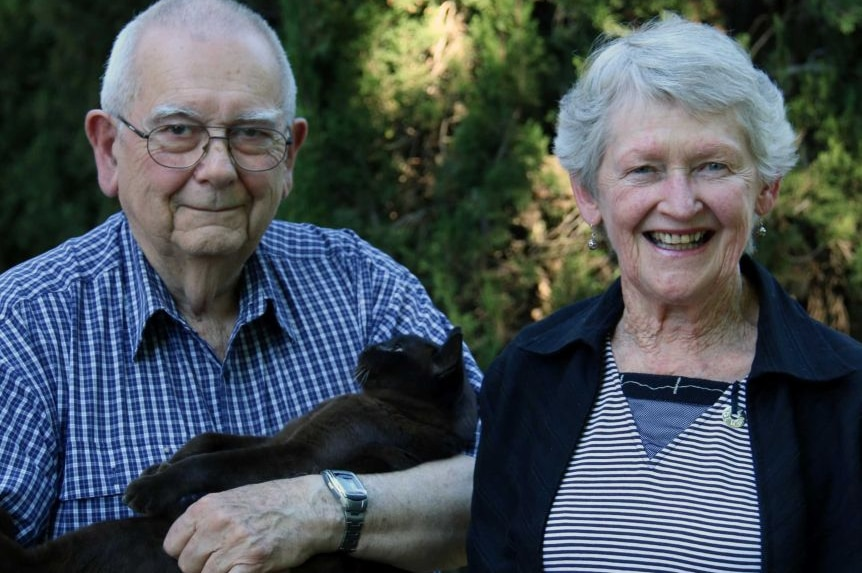 Mike Saclier stands with his wife Wendy, holding a black cat.