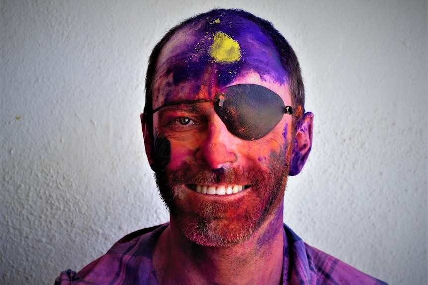 A picture of blind photographer Kristan Emerson, covered in colourful powder after attending the Holi Festival in India